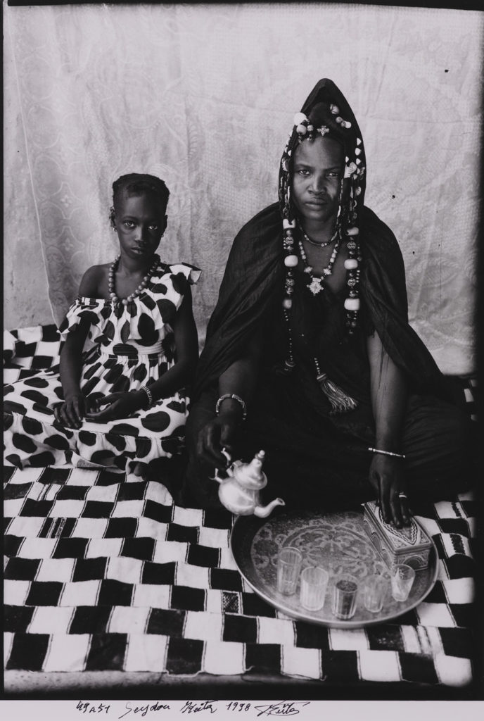 A Moorish Haratine Woman Posing With Her Daughter On A Chequered Blanket